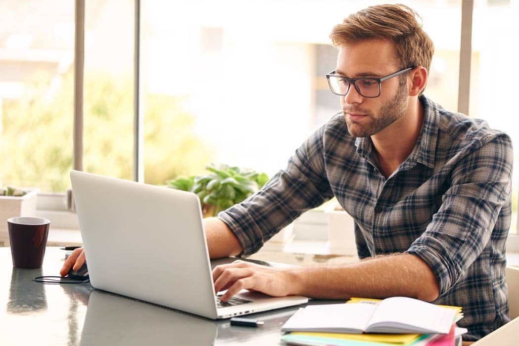 Photo of a young man with glasses working on his laptop computer.