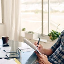 Photo of a young man writing on a pad of paper in front of his computer.