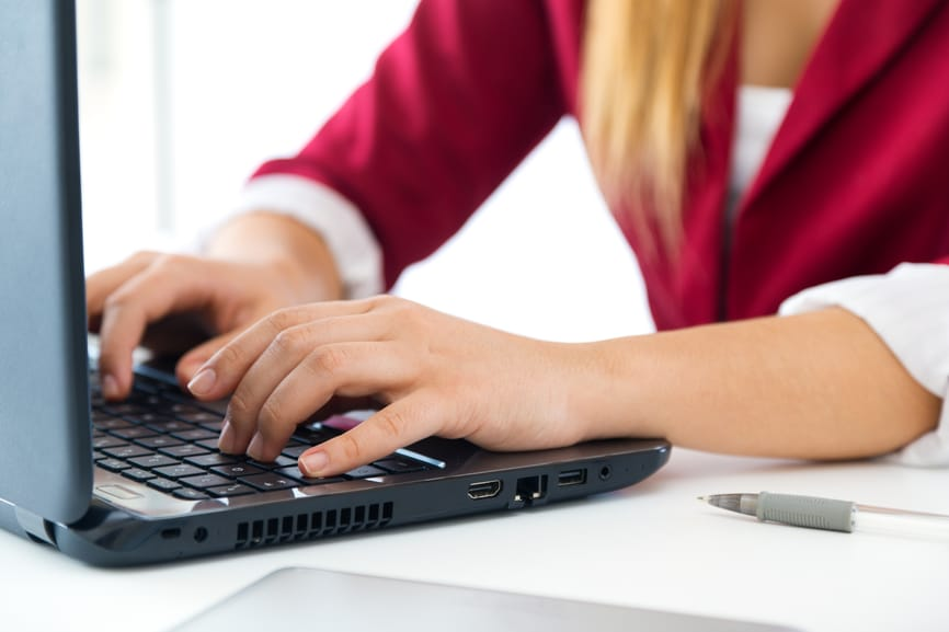 Photo of a business woman typing on a laptop.