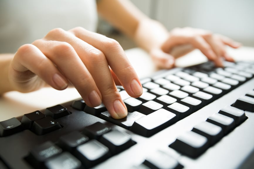 Photo of a person typing on a computer keyboard.