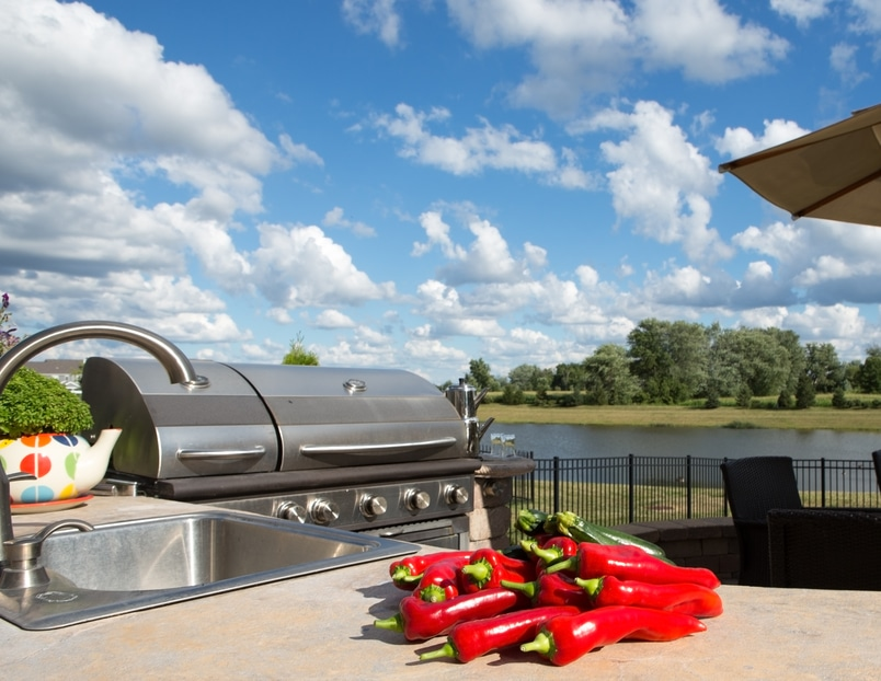 Backyard patio with an outdoor kitchen, with chili peppers on the countertop.