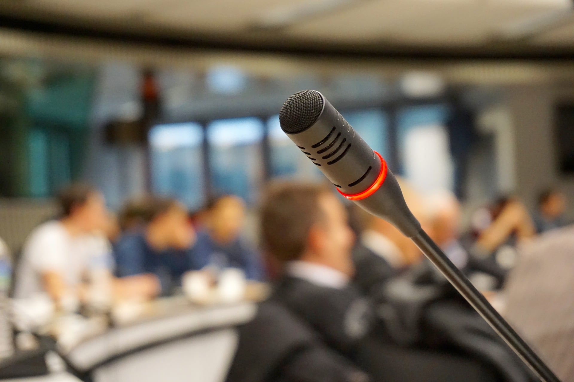 Photo of a microphone with people sitting in the background.