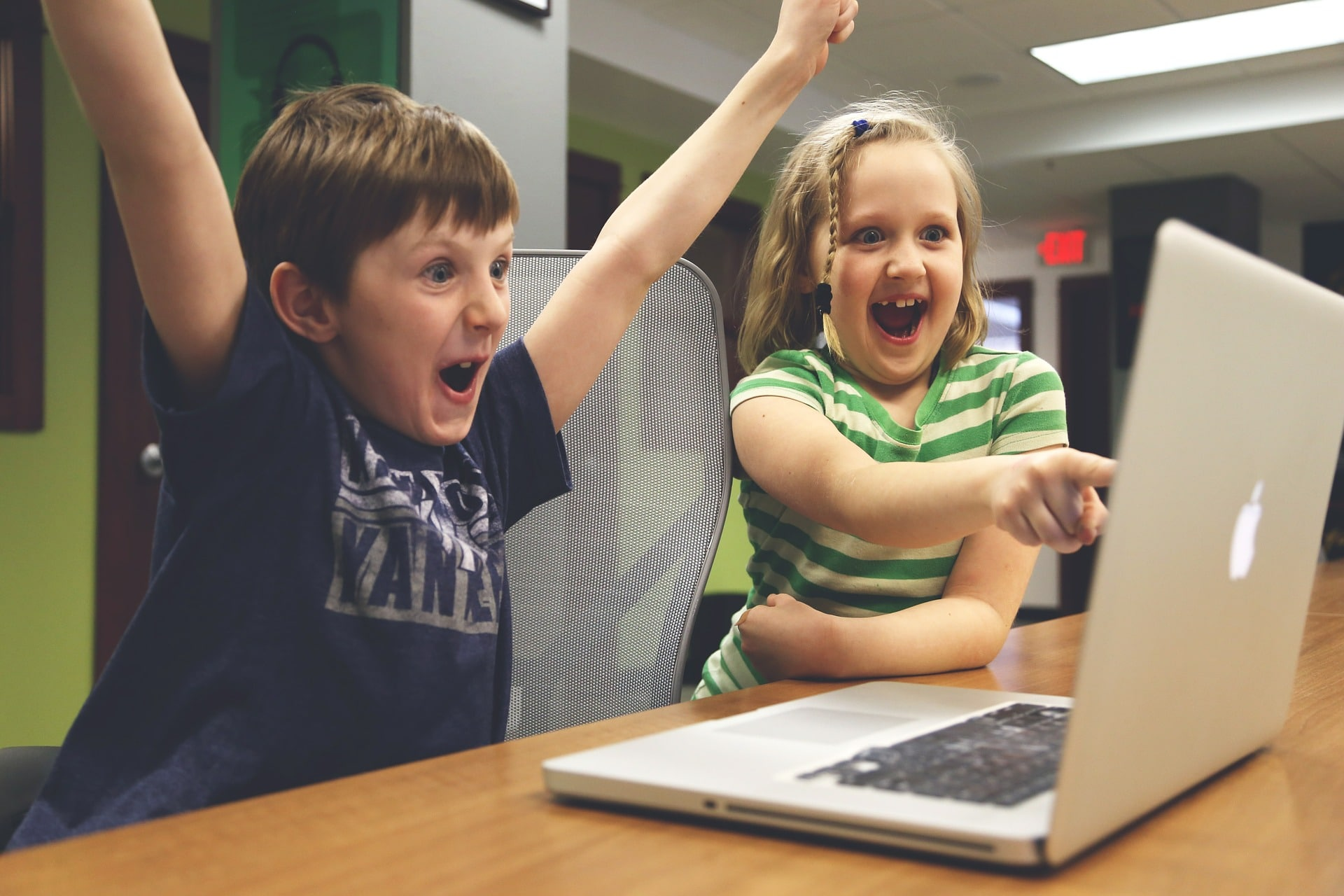 Photo of 2 children excitedly watching a video on a laptop.