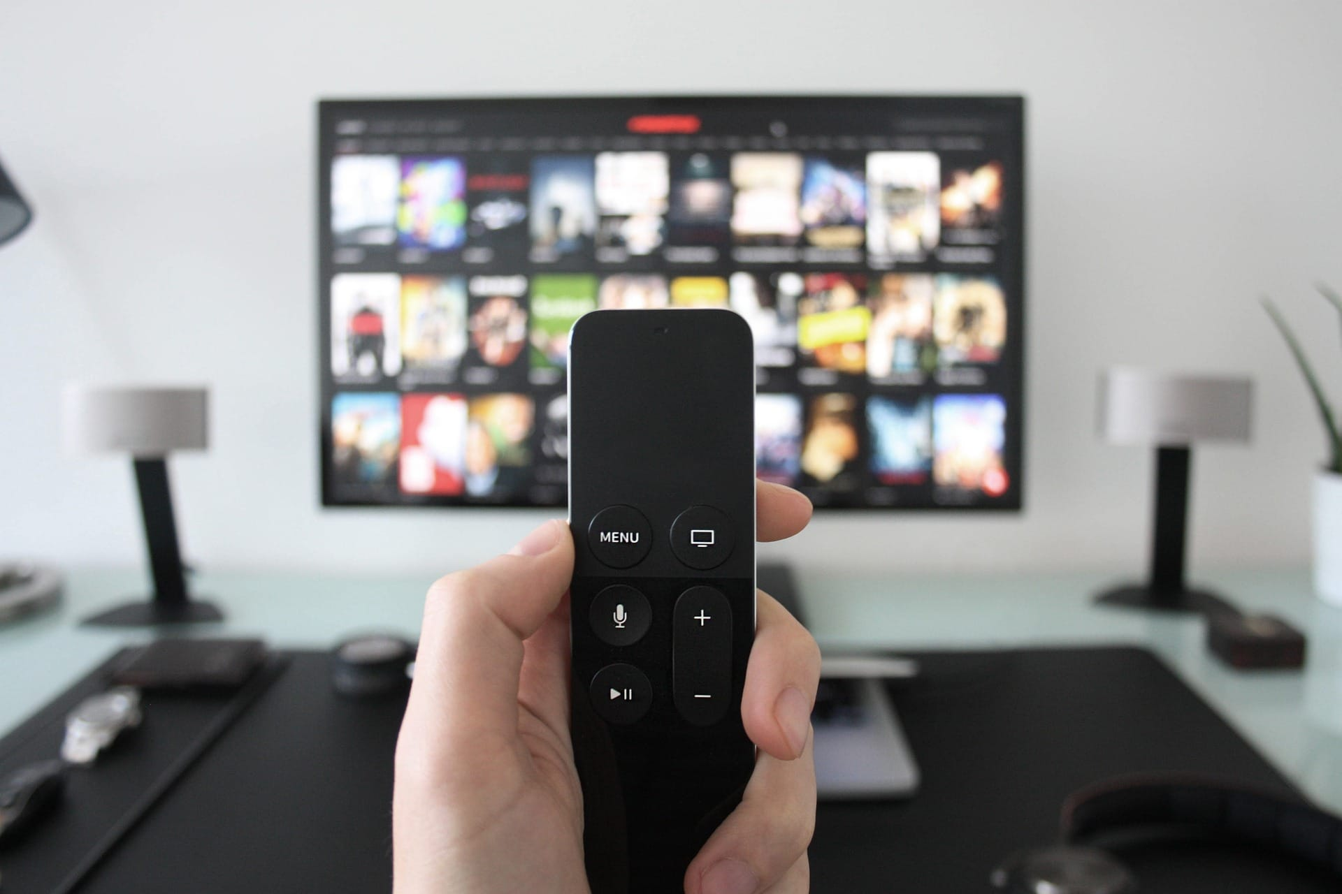 Photo of a person holding a remote in front of a TV.