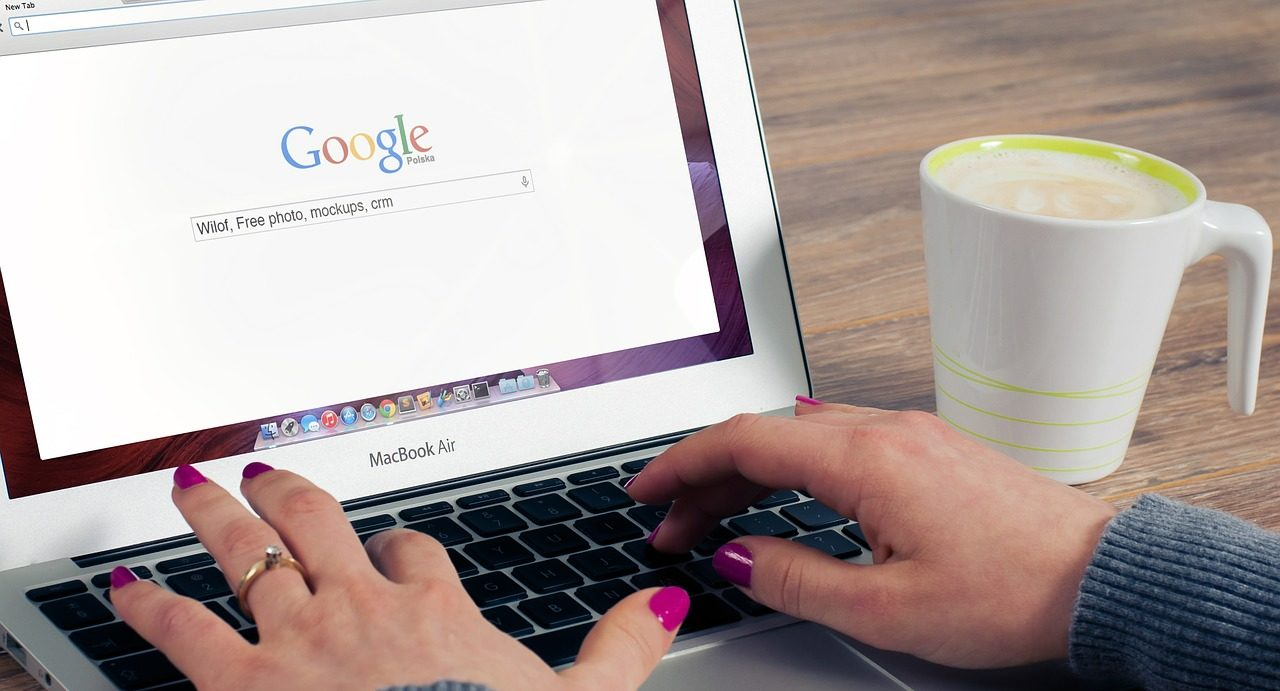 Photo of a woman using Google to search on a computer.